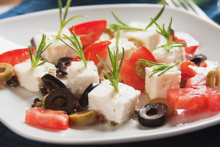 Cheese, tomato and olives salad with rosemary and olive oil photo