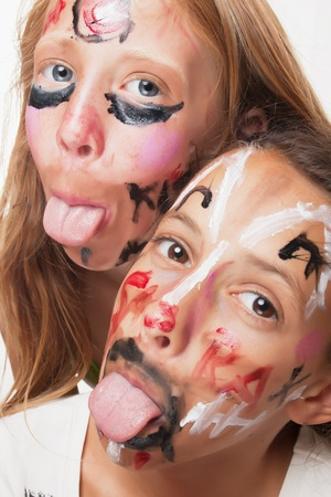 tongue out: Two young girls with faces painted for carnival parade