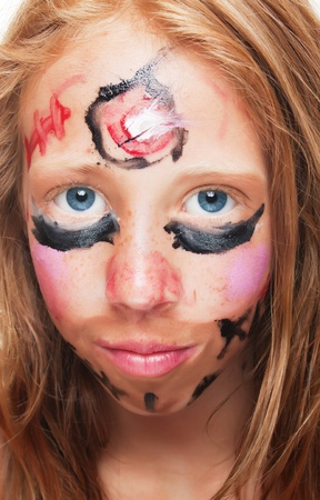 angry child: Red haired young girl with face painted for carnival parade
