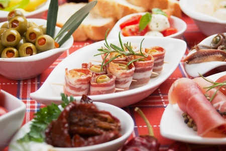Bacon rolls with olives and other antipasto or tapas food