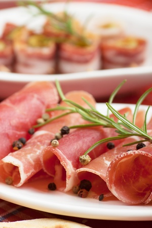 cured ham: Slices of prosciutto, italian cured ham with rosemary and peppercorn, selective focus