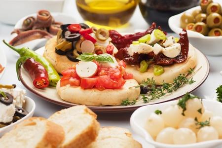 tapas españolas: Tapas con queso, tomate, aceitunas, albahaca, pimientos, enfoque selectivo Foto de archivo