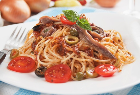 Spahgetti a la puttanesca with anchovy, caper, tomato and olives photo