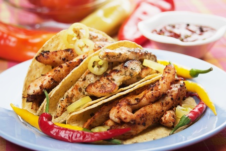 Grilled chicken meat and hot chili peppers in taco shells Foto de archivo