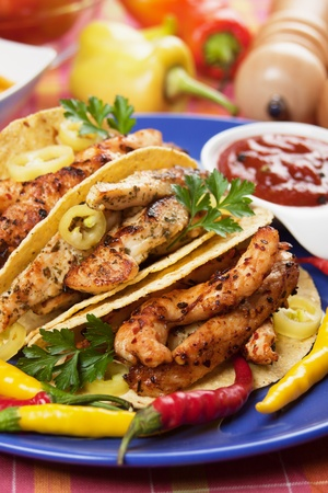 chicken meat: Grilled chicken meat and hot chili peppers in taco shells Stock Photo