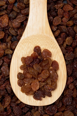 raisins: Raisin, dried sweet grape fruit on wooden spoon