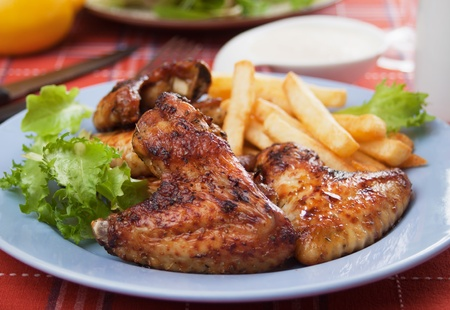 Oven roasted chicken wings with french fries  and lettuce photo