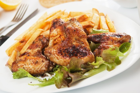 Grilled chicken wings served with lettuce and french fries Stock Photo - 11834934
