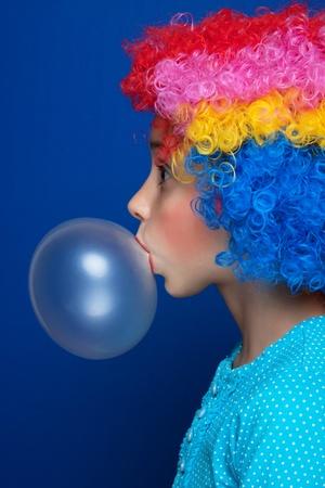 -Guma do żucia: MÅ'oda dziewczyna dmuchanie balonu gumy do żucia na niebieskim tle Zdjęcie Seryjne