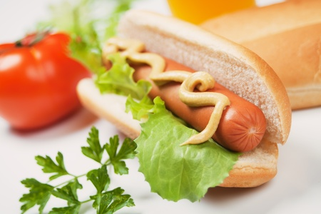 hot dog sausage and bun with mustard and lettuce