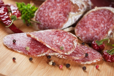 salami: Sliced salami with herbs and pepper on wooden board Stock Photo