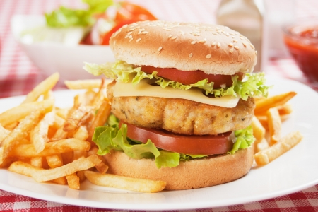 Delicious chicken burger with cheese, tomato and lettuce Standard-Bild