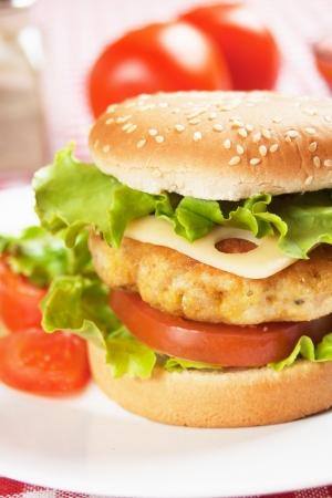 hamburguesa de pollo: Deliciosa hamburguesa de pollo con queso, tomate y lechuga Foto de archivo