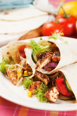 Grilled chicken meat and vegetable salad in tortilla wrap photo