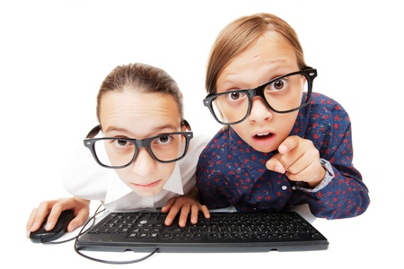 Two girls playing or working on a computer, isolated over white background