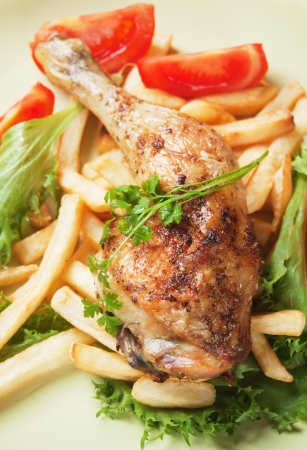 Roasted chicken leg with french fries, lettuce and tomato photo