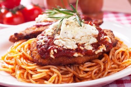 Chicken parmesan, breaded chicken steak with tomato sauce and spaghetti pasta Foto de archivo