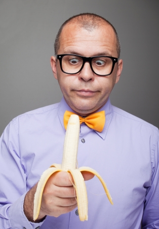 eating banana: Weird man eating banana fruit, studio shot Stock Photo