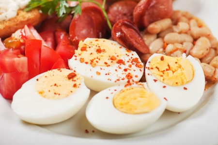 hard boiled: Hard boiled chicken eggs with beans and sausage served for breakfast Stock Photo