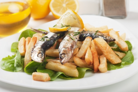 Grilled sardine wish served with french fries and lettuce photo