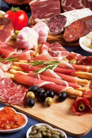 antipasto: Italian prosciutto, cured pork meat on cutting board