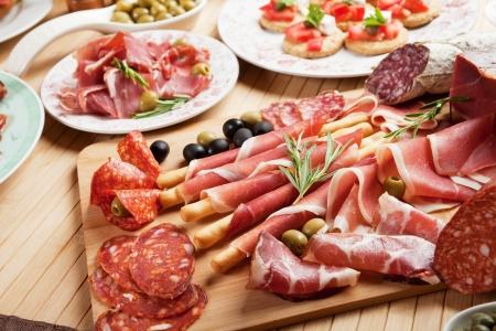 Italian prosciutto, cured pork meat on cutting board