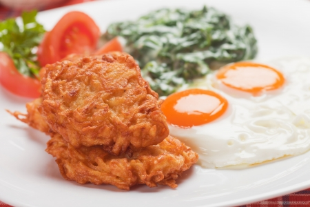 sunny side up: Fried potato pancakes served for breakfast with spinach and eggs Stock Photo