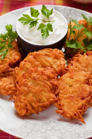 Latkes, hebrew potato pancakes served with sour cream photo
