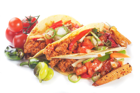 Taco shells filled with ground beef and fresh vegetable photo