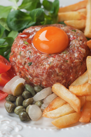 Tartar steak, raw meat steak with egg yolk, onion and french fries Imagens