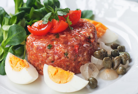 ground beef: Tartar steak, raw meat steak with capers, onion and egg Stock Photo