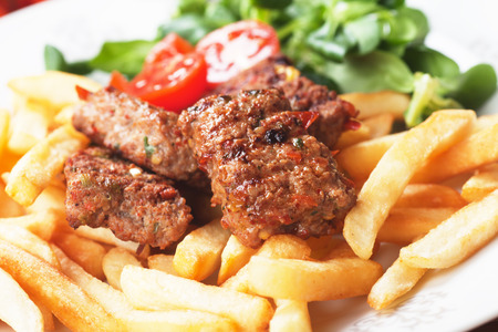 ground beef: Square burgers, spicy barbecued bites with french fries and salad Stock Photo