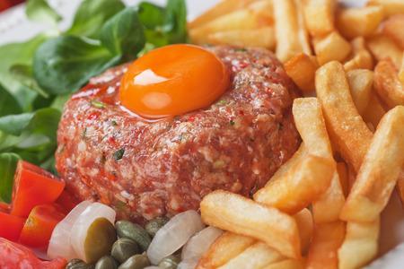 steak tartare: Tartar steak, raw meat steak with egg yolk, onion and french fries Stock Photo