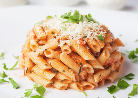 grated parmesan cheese: Italian penne rigate pasta with tomato sauce, grated parmesan cheese and parsley