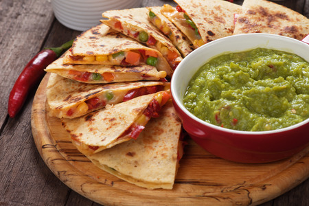 Mexican quesadillas with cheese, vegetables and guacamole dipping sauce