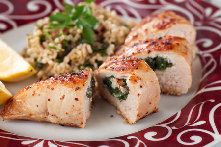 Grilled chicken breast stuffed with spinach, served with bulgur wheat salad 스톡 콘텐츠