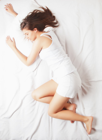 Young girl sleeping in bed on white sheets, shot from above