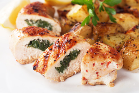 Stuffed chicken breast with roasted potato and lemon slices photo
