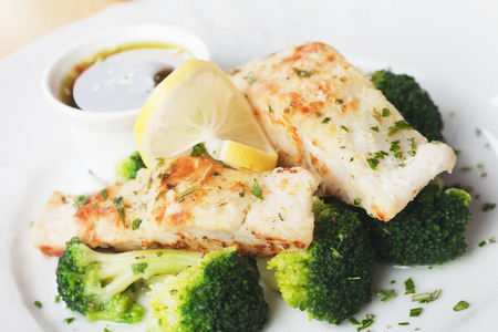 Grilled cod fish steak with broccoli and lemon