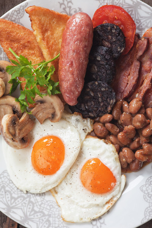 english breakfast: Full english breakfast with fried eggs, bacon, mushrooms, sausage and kidney beans