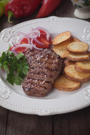 carne asada: Grilled beef steak with roasted potato and tomato salad
