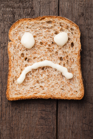 sad smiley: Sad smiley made from mayonnaise on slice of bread Stock Photo