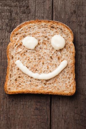 smiley content: Souriant heureux fabriqu� � partir de la mayonnaise sur tranche de pain Banque d'images