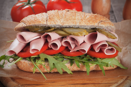 bologna baloney: Submarine sandwich with baloney, pickles, tomato and rocket salad