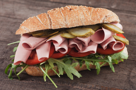 bologna baloney: Submarine sandwich with bologna sausage, pickles, tomato and rocket salad