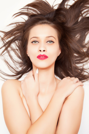 femme fatale: Beautiful brunette girl with long hair, studio shot on white background