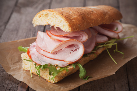 Submarine sandwich with smoked ham, tomato and lettuce salad
