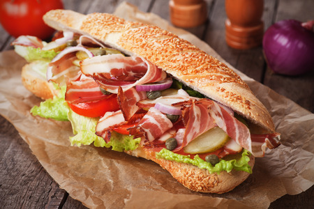 processed food: Submarine sandwich with bacon, caper, tomato and lettuce salad Stock Photo