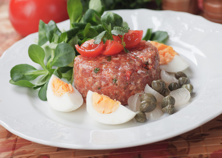 ground beef: Tartar steak, raw ground beef meal with boiled eggs, capers and cherry tomato