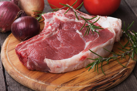 Raw ribeye beef steak on wooden board with rosemary and onion Stock Photo